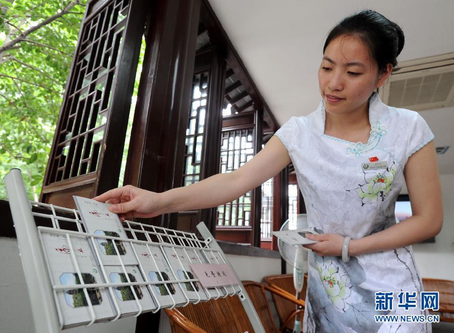 """6月8日,苏州虎丘山风景区一名换上""""荷花""""主题新装的导游在整理宣传册."""