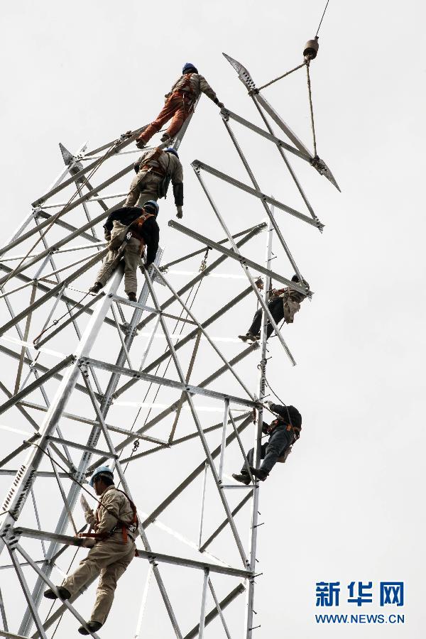 泰州供电公司线路施工人员在高空组立铁塔