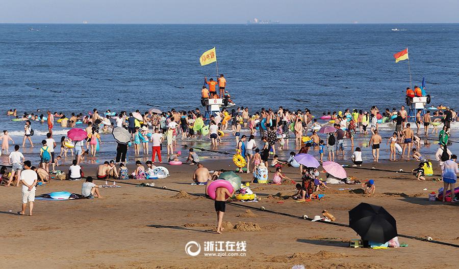 7月26日,舟山东沙湾海滨浴场人头攒动,大批游客及市民到这裏享受大海
